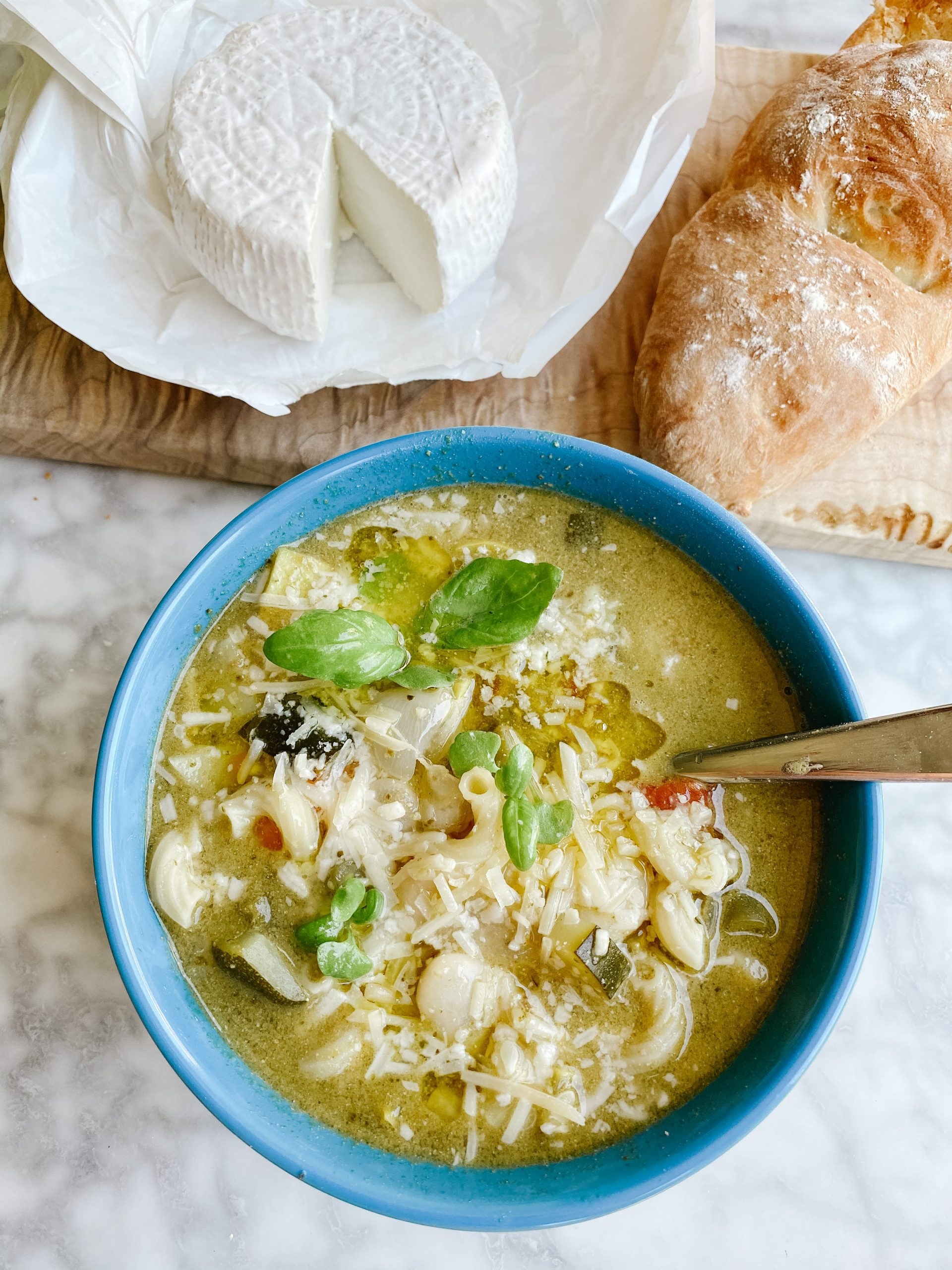 Soupe au Pistou in a blue bowl with baguette and goat cheese