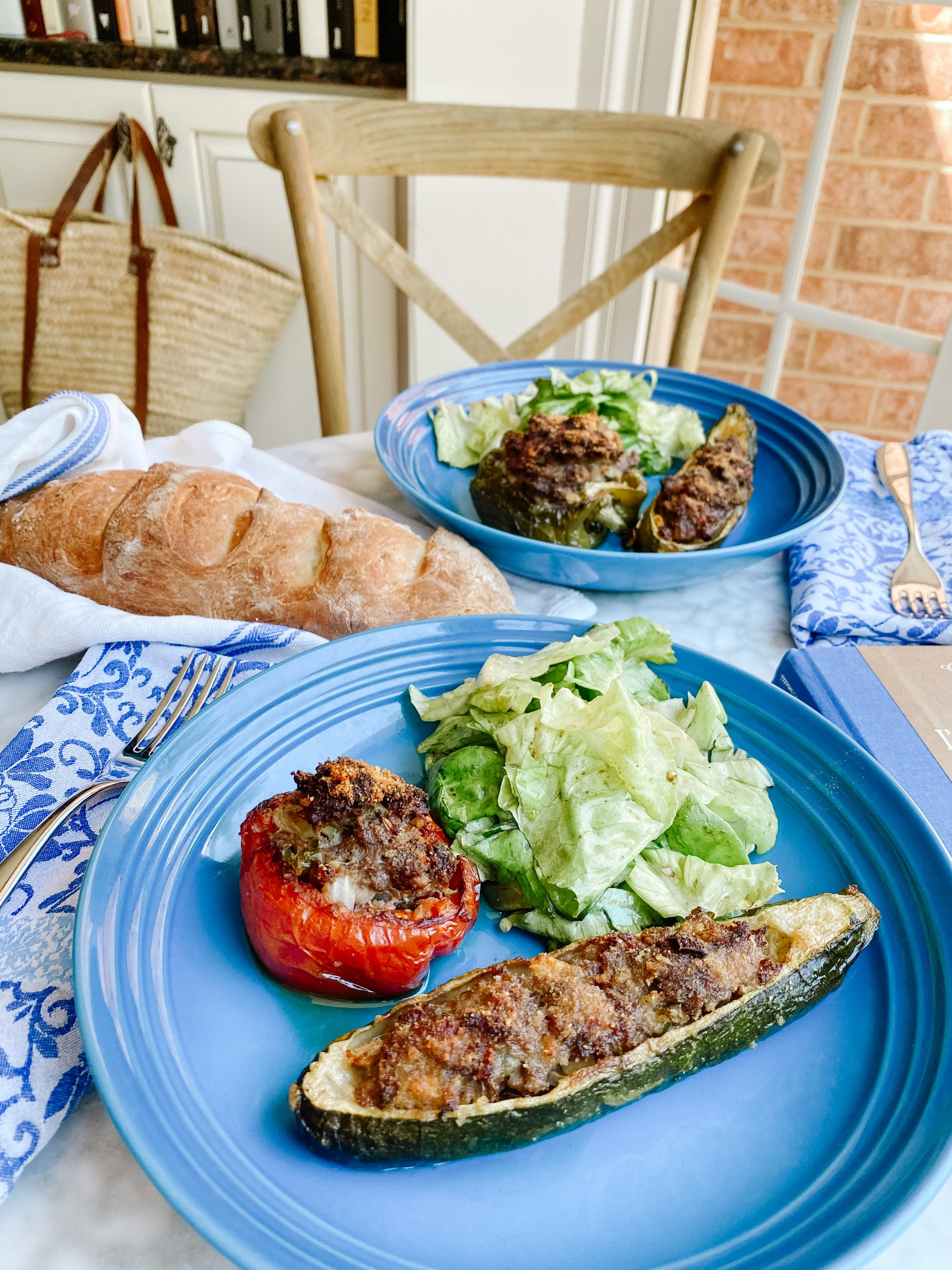 Petits Farcis Provençale or Petits Farcis Niçois on a blue plate with a serving of salad and a french baguette