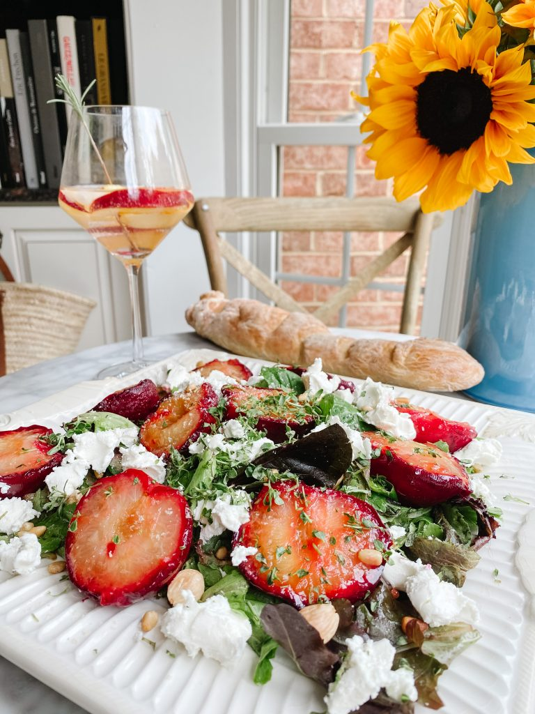 roasted plums, goat cheese and lemon thyme with a glass of rosé and a sunflower on a table