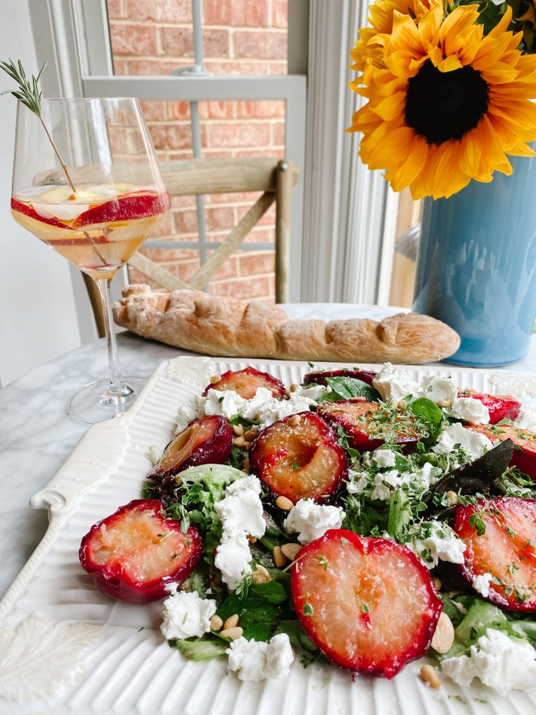 roasted plums, goat cheese salad with a glass of wine and a french baguette and a sunflower