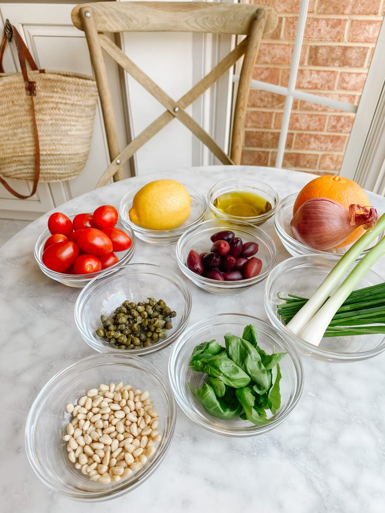 Glass bowls with the ingredients for Branzino sauce. Pine nuts, capers, basil, chives, olives, cherry tomatoes and lemon