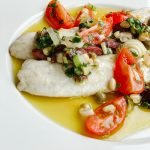Oven baked Branzino with Vierge sauce made with tomatoes, olives, onions, basil