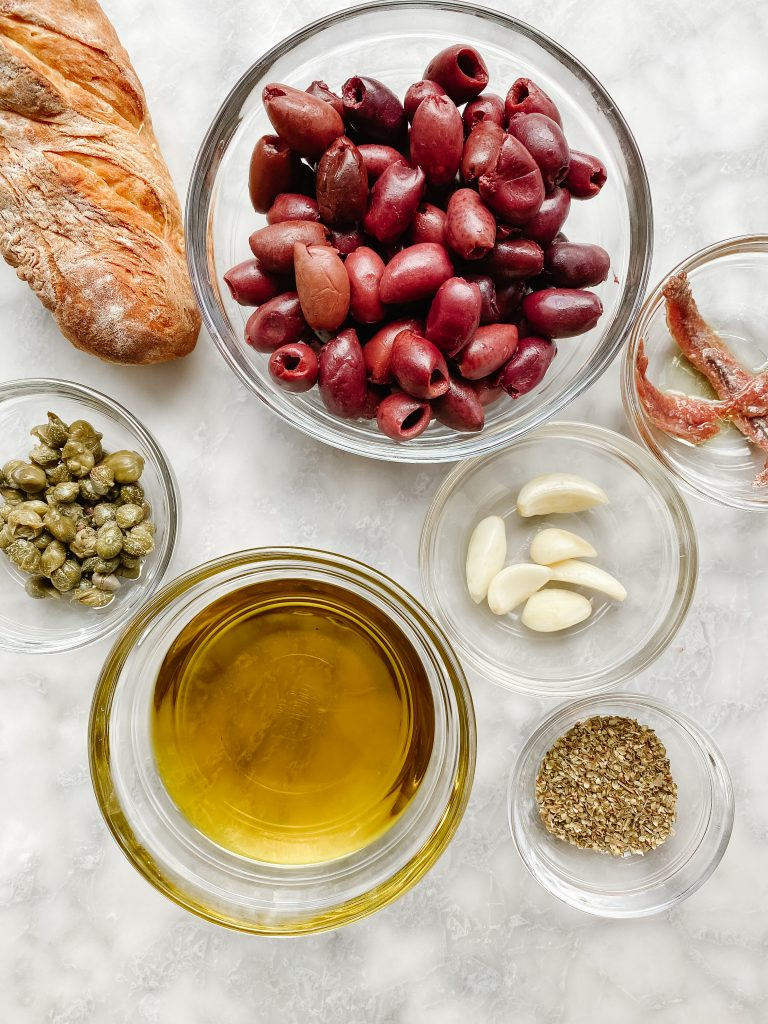glass bowls with French Riviera ingredients. Olive oil, olives, garlic, herbes de provence, capers
