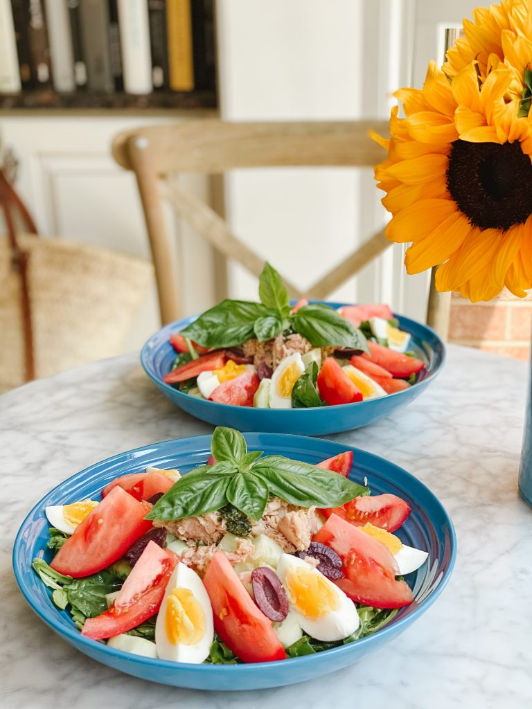 tomatoes, eggs, cucumbers, olives lettuce, tuna and basil on two blue plates with a sunflower