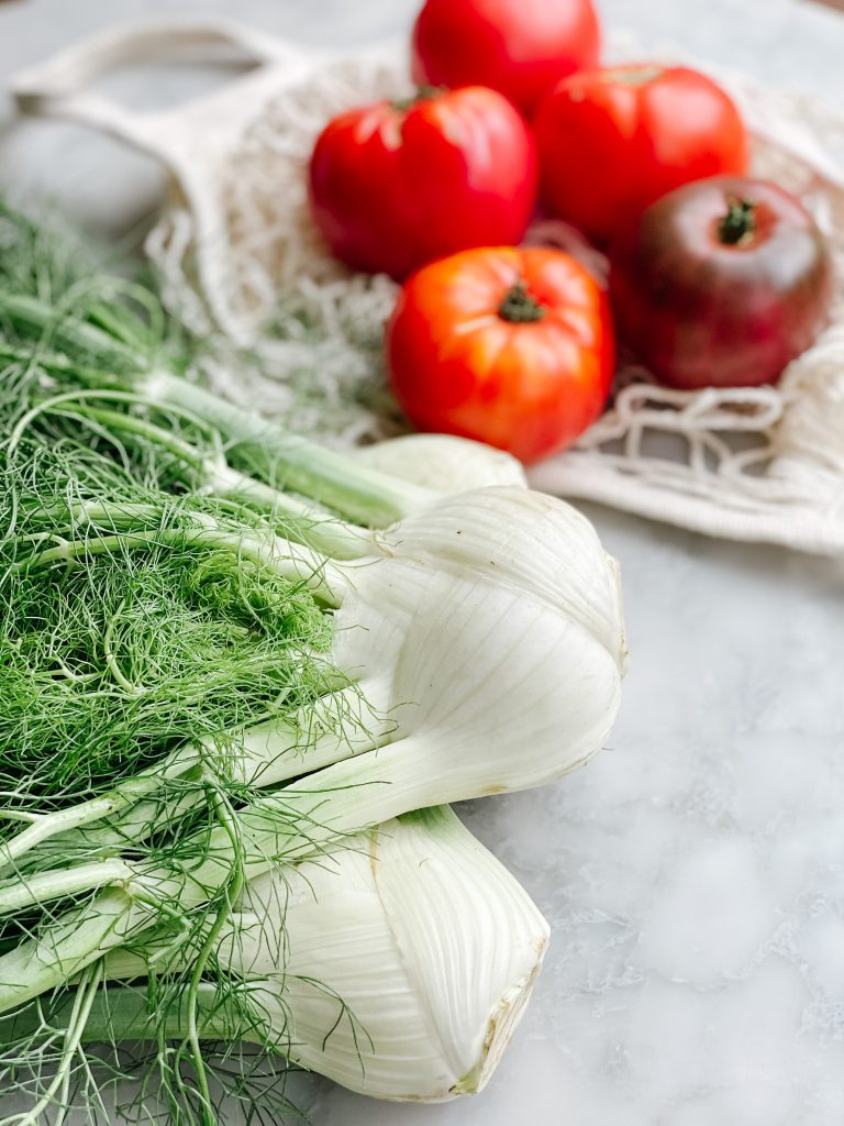 Fresh Fennel bulbs and tomatoes on a marble table