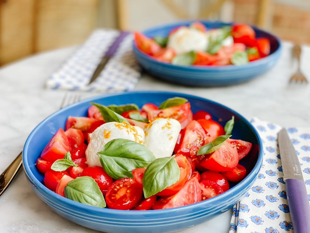 tomato basil salad in a blue bowl on a marble table with a napkin and a knife