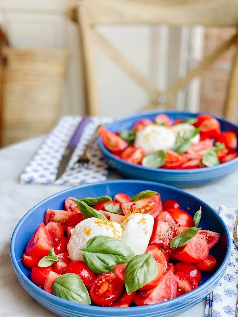 2 blue bowls on a table with tomato burrata salad. a chair in the background