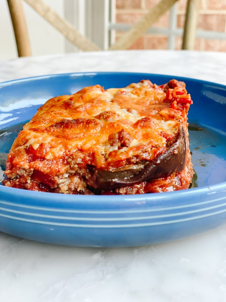 a blue Le creuset dish with a slice of Eggplant lasagna on a marble table