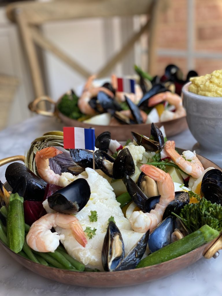 2 copper plates with Le Grand Aïoli, shrimp, cod, fresh vegetables, mussels a french baguette and aïoli
