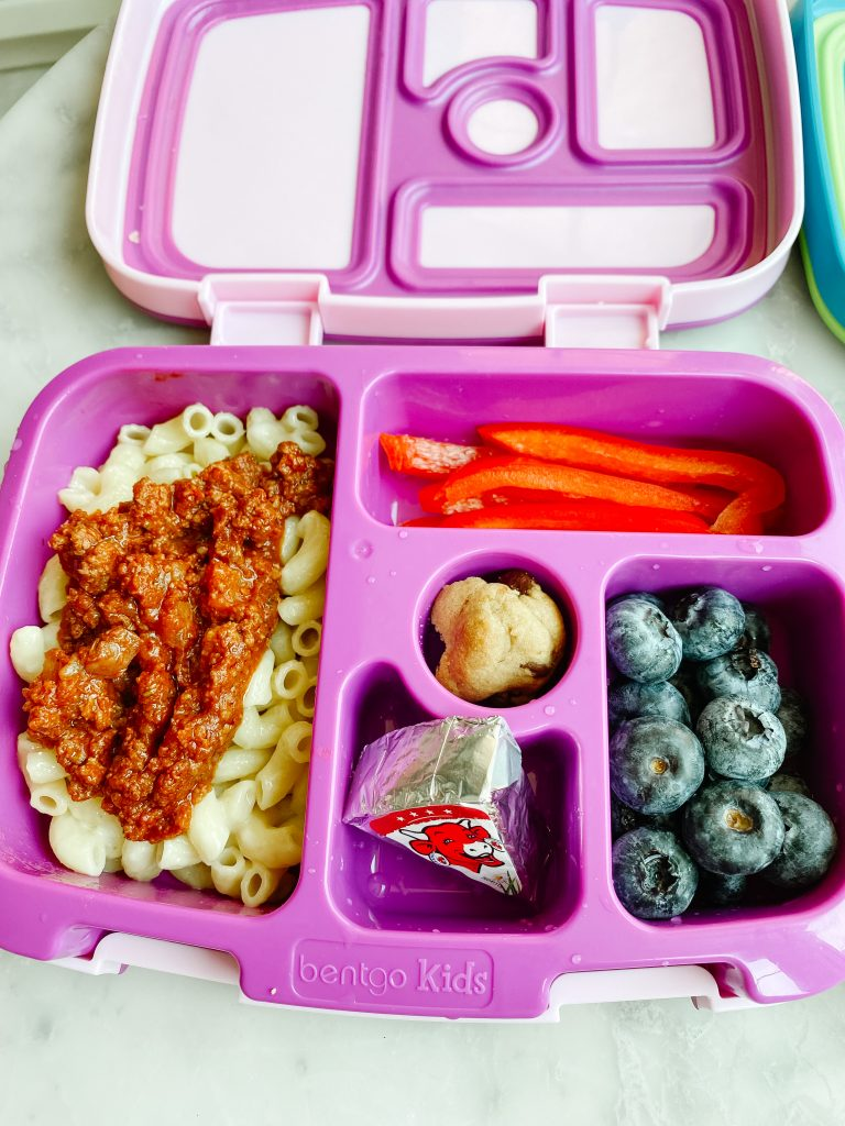 pasta with meat sauce, sliced peppers, blueberries and cheese in a lunch box