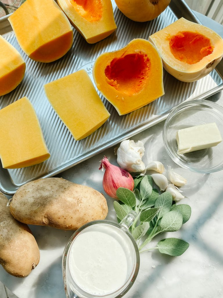Ingredients for butternut squash soup with cream and sage on a table