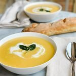 two bowls butternut squash soup with cream and sage on a table with a fresh baked baguette